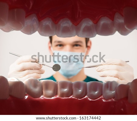 View at young male dentist holding dental tools from patient mouth  - stock photo