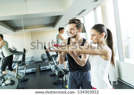 View at Young woman in gym exercising with her personal trainer
