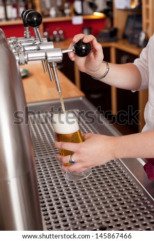View behind the counter in a bar or club of a woman dispensing fresh draft beer into a pint glass from a metal spigot - stock photo