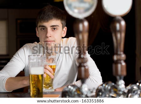 View between the beer taps on a dispenser of a serious young man drinking alone at the counter in the bar or pub