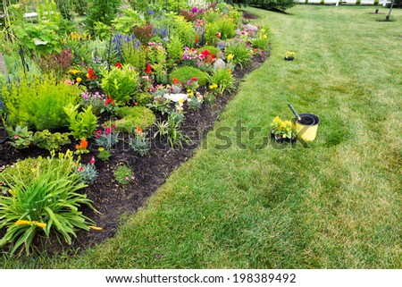 View down the length of a beautiful landscaped flowerbed filled with flowering and ornamental plants bordered by a lawn with seedlings of yellow celosia for planting - stock photo