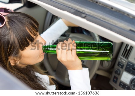 View down through the sunroof of a middle-aged woman drinking alcohol from the bottle while driving a car - stock photo