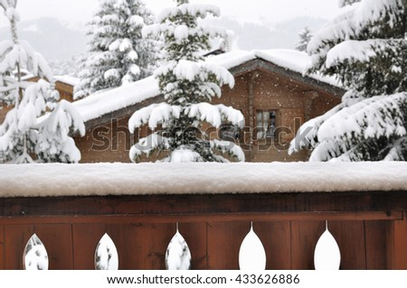 view from a balcony of snowfall in a village with wooden cottage and firs