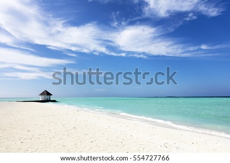 View from a beach on a tropical, paradise island with a blue sky above and a beautiful turquoise sea.