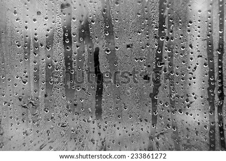 View from a car window during rain with smashed droplets as a weather background. Black and white conversion with filters applied - stock photo