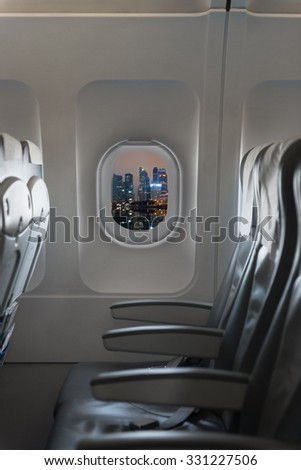 View from a commercial aircraft showing the beautiful cityscape at night through the cabin window and the comfortable chairs - stock photo
