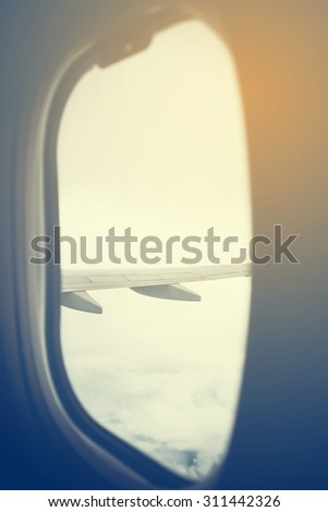View from a jet plane window high on the blue skies with Airplane flying for blur blackground.vintage - stock photo
