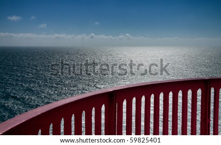 view from a lighthouse in norway with bright sunlight and a red rail