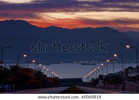 view from a local street on the gulf of aqaba one hour before sunrise - stock photo