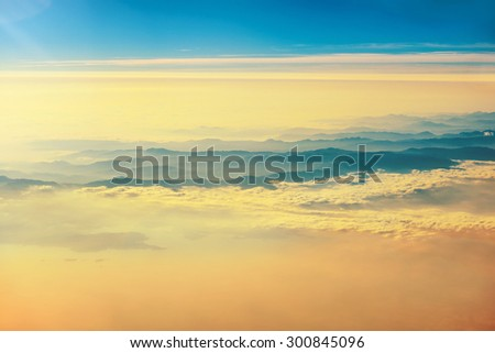 View from a plane to orange sunset on the sky with sunrays. Fluffy clouds background - stock photo