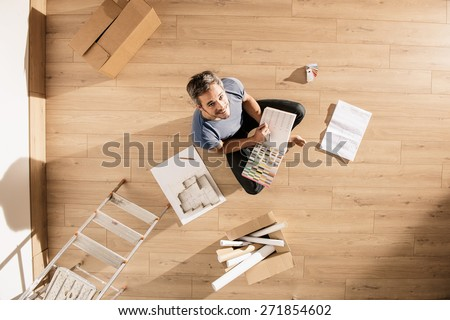 view from above, looking at the camera a man sitting on the floor of his new home, there are blueprints and samples colors to help him to think about his new interior decoration - stock photo