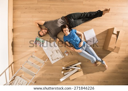 view from above, looking at the camera a young couple lying on the floor of their new home, there are blueprints to help them to think about their new interior decoration - stock photo