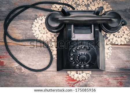 View from above of a black old-fashioned rotary telephone instrument on a crocheted doily on a weathered wooden table top - stock photo