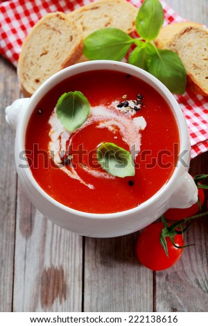View from above of a delicious bowl of fresh country tomato soup garnished with cream and basil and seasoned with pepper, served with sliced baguette - stock photo