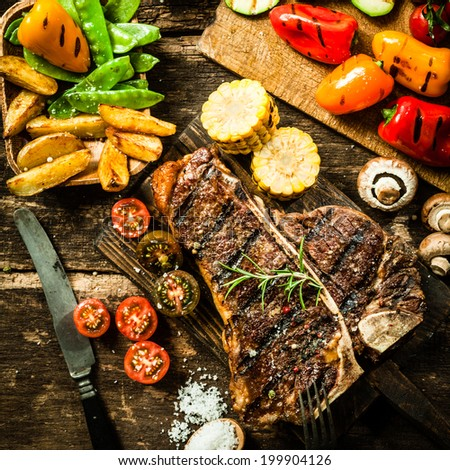 View from above of a delicious grilled porterhouse steak with assorted roast vegetables including tomato, peppers, mushrooms, corn, mangetout, and potato wedges - stock photo