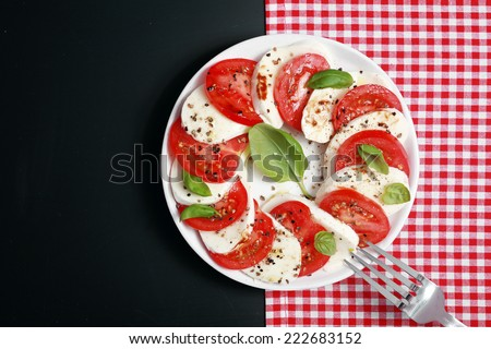 View from above of a plate of Italian Caprese salad with colorful alternating slices of tomato and mozzarella cheese seasoned with basil and pepper on a red and white check and dark grey background - stock photo
