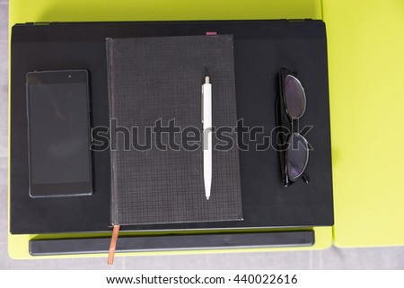 View from above of a tabletop workstation with closed laptop, a diary, glasses and mobile phone are arranged in strict order on it - stock photo