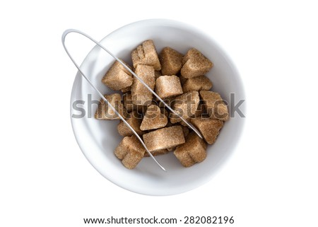 View from above of brown sugar cubes in a bowl with a pair of tongs for serving, isolated on white - stock photo