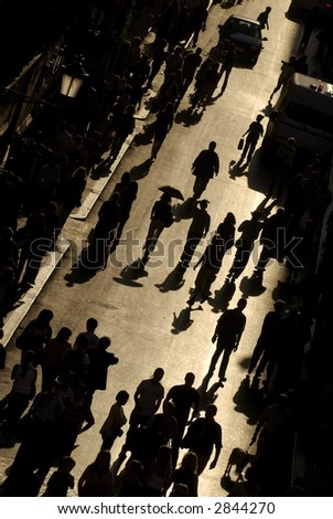 view from above of busy street with people walking silhouetted against golden light in rome italy - stock photo