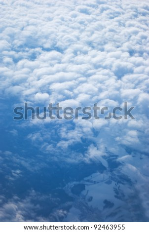 View from above of earth through clouds - stock photo