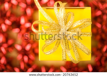 View from above of golden ribbon on top of present box surrounded by red decorations - stock photo