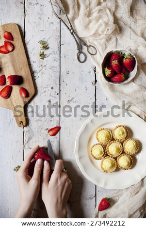 view from above of hands preparing little tartlets with pastry cream and sliced strawberries on rustic table