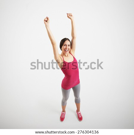 view from above of happy sportswoman in sport wear raising her hands up and laughing over light grey background - stock photo