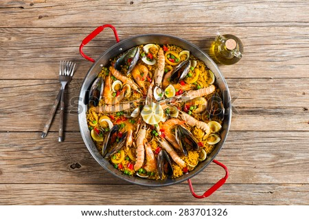 View from above of paella with seafood in a paellera on a wooden background with copy space - stock photo