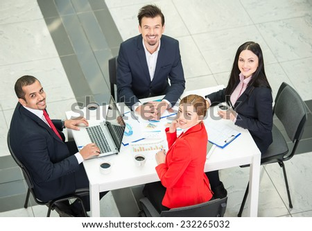 View from above of several business people are planning work around table. They are looking at the camera. - stock photo