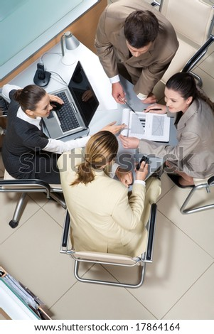 View from above of successful business partners sitting at table and interacting - stock photo