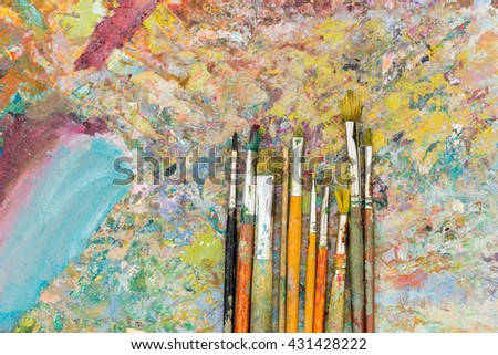 View from above of time-worn paintbrushes on an old colorful palette - stock photo