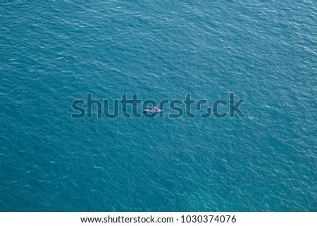 View from above of tourist canoeing in the ocean