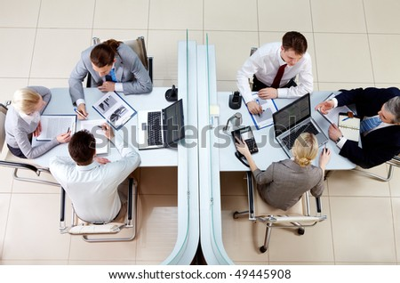 View from above of two business teams working and interacting separated by border in office - stock photo