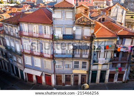 View from above on a block of apartment buildings in Porto, Portugal, with the typical tiles on the wall and laundry hanging out of the windows - stock photo
