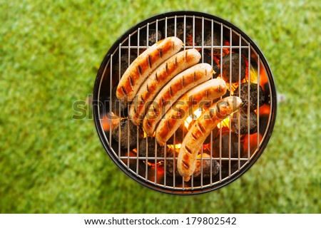 View from above on a green grass background of a row of pork and beef bratwurst grilling over a barbecue fire on a hot day during the summer vacation - stock photo