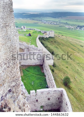 View from above portraying the massive ruined fortification walls and part of vast courtyard of famous Spissky Castle (Spissky hrad) during late evening before sundown. - stock photo