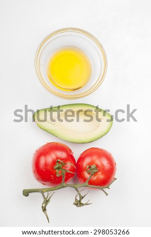 View from above to the tomatoes, avocado and olive oil on light background - stock photo