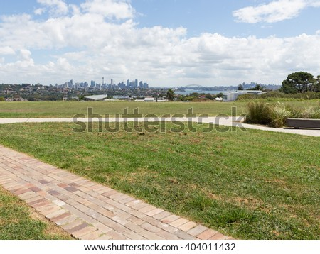 View from afar on the skyscrapers of Sydney and the famous Sydney Harbour Bridge from the observation deck during the day, Australia - stock photo
