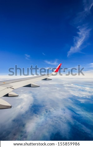 view from airplane window with airplane wing blue sky and white clouds - stock photo