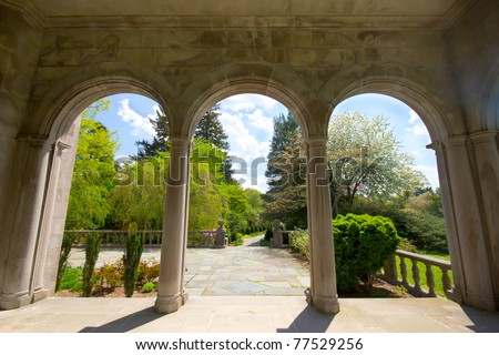 View from arched portico looking out into the gardens at historic Long Island Gold Coast Mansion - stock photo