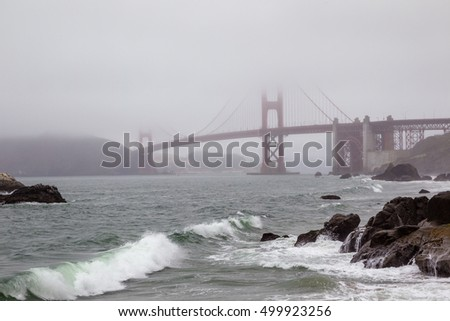 View from Baker Beach to Golden Gate Bridge in San Francisco, California, USA on a foggy day.