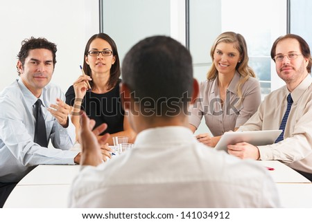 View From Behind As CEO Addresses Meeting In Boardroom - stock photo