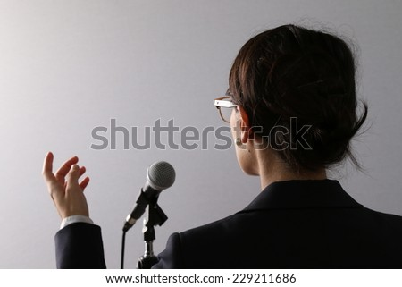View from behind of a businesswoman standing in front of a microphone gesturing as she gives a presentation or speech - stock photo