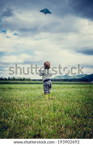 View from behind of a cute young child in gumboots standing flying a kite in a grassy green field standing holding the string watching it soar in the air above open countryside. - stock photo