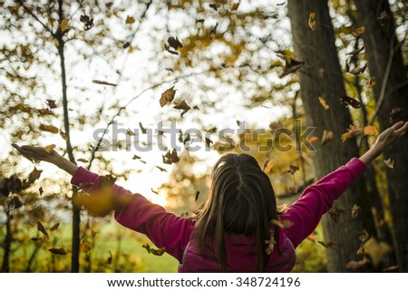 View from behind of a young woman standing in autumn woods with her arms outstretched while leaves are falling on her and the evening sun lights the atmosphere.