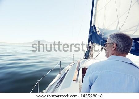 view from behind of sailing man on hobby boat at sea - stock photo