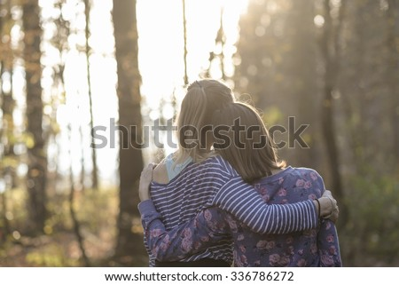 View from behind of two girlfriends or a lesbian couple standing in autumn woods leaning on each other with their arms around one another. - stock photo