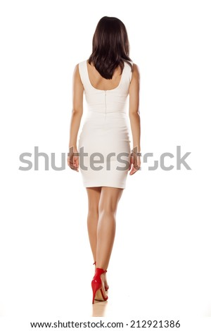 view from behind on young woman in a short white dress - stock photo