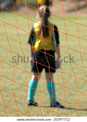 View from Behind the soccer  goal net onto the field with goalie
