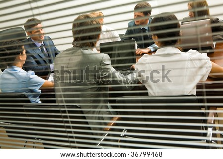 View from behind venetian blind of associates interacting at working meeting - stock photo